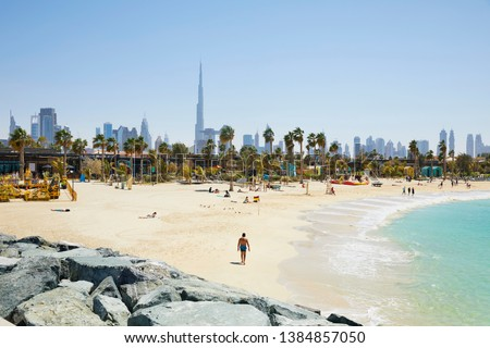 The beach of 'La Mer' (The Sea) with in the background the skyline of Dubai, United Arab Emirates Royalty-Free Stock Photo #1384857050
