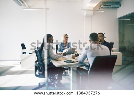 Smiling group of diverse coworkers talking together during a meeting around a table inside of a glass walled office Royalty-Free Stock Photo #1384937276