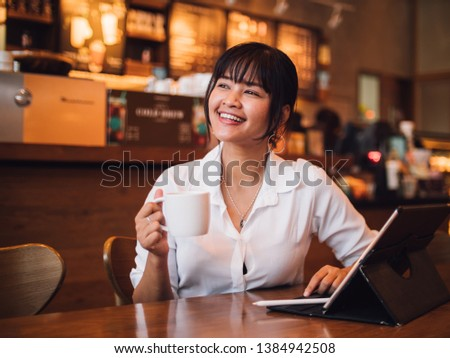 Asian woman drinking coffee in cafe and using laptop computer for working business online marketing #1384942508