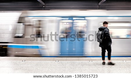 subway train arriving to modern metro station with male passenger person waiting on platform blurred background side view of city transportation underground station with motion car and people #1385015723