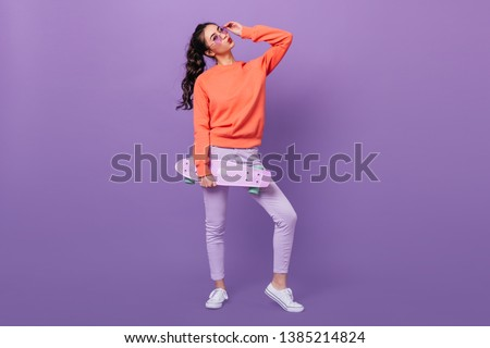 Full length view of trendy korean girl with skateboard. Studio shot of gorgeous asian woman holding longboard on purple background. #1385214824