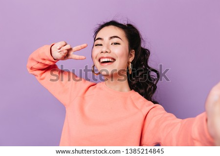 Lovely korean girl posing with peace sign. Laughing asian young woman taking selfie on purple background. #1385214845