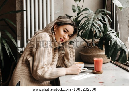 Blonde Asian girl in beige oversized sweater sits in cafe with cup of coffee and carrot juice