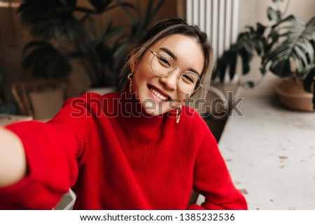 Lady in glasses and massive earrings makes selfie. Asian girl dressed in red knitted sweater posing against background of plants in room #1385232536