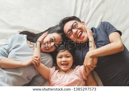 Happy Asian family laying on bed in bedroom with happy and smile, top view #1385297573