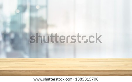 Wood table top on blur window glass,wall background with city view.For montage product display or design key visual layout #1385315708