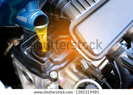 Refueling and pouring oil quality into the engine motor car Transmission and Maintenance Gear .Energy fuel concept. #1385319485