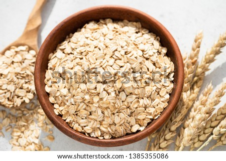 Oats, oat flakes or rolled oats in a bowl. Closeup view. Healthy clean eating food, healthy lifestyle concept #1385355086