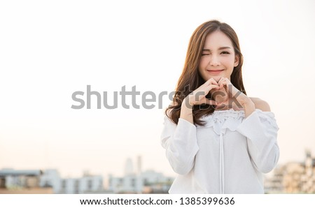 Portrait of young beautiful asian woman hands gesture in heart shape on city sky roof top. Smile face asian girl wear casual cloth. Japanese girl lifestyle, lovely woman valentines' day concept  #1385399636