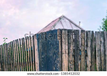 Old Rustic Wooden Board Fence with the Roof of a House and Garden behind At Sunset #1385412032