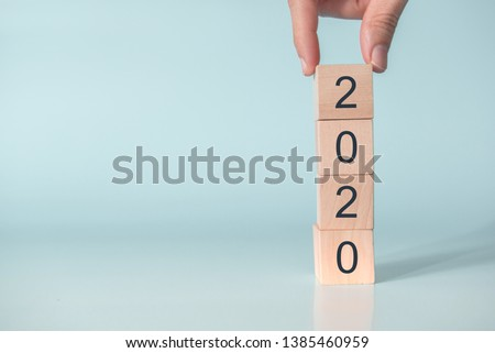 Hand of man putting wood cube shape with text new year 2020, copy space. #1385460959