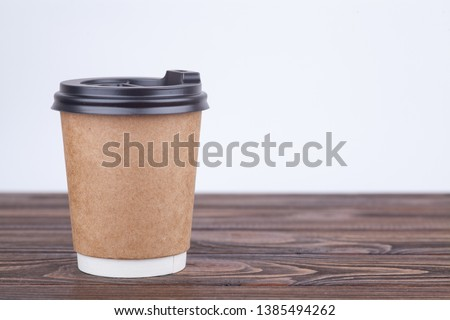 Craft paper coffee cups on a table near light wall background #1385494262