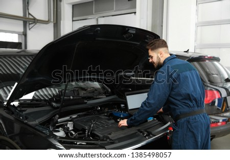 Technician checking car with laptop at automobile repair shop #1385498057
