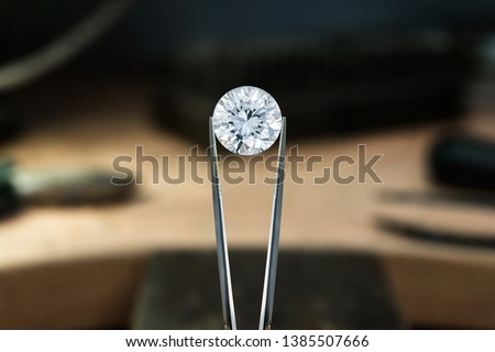 Beautiful diamond stone in tongs. Craft jewelery making with professional tools in jeweller studio. Putting the diamond on the ring. Macro shot. A handmade jeweler process, manufacture of jewellery. #1385507666