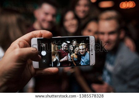 Focused photo. Picture of girl taking photo of herself and her friends at the party.
