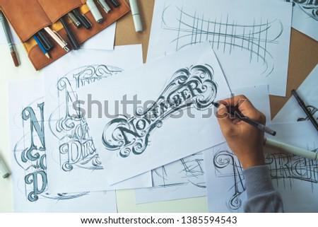 Typography Calligraphy artist designer drawing sketch writes letting spelled pen brush ink paper table artwork.Workplace design studio. #1385594543