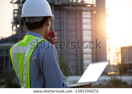 Engineers male working with laptop and operate the radio for workers security control at power plant. Energy power station area with sky, sunset. Concept safety,industry #1385596076