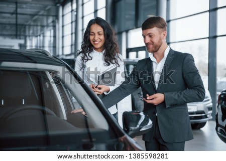 In good mood. Female customer and modern stylish bearded businessman in the automobile saloon. #1385598281