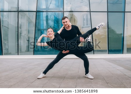 two gymnasts guy and girl in black clothes on the background of colored glasses #1385641898
