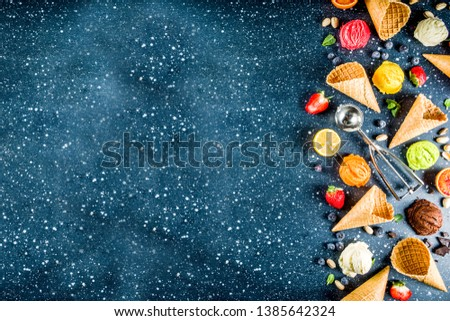 Colorful fruit and berry, nut, chocolate and vanilla ice cream, with waffle ice-cream cones, with fresh fruit and berries, top view copy space dark blue background