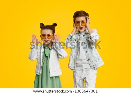 Astonished girl and boy in stylish outfits gesturing with hands and looking at camera while standing against bright yellow background #1385647301