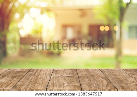 wooden table space with green home backyard view blur background for advertising template #1385647517