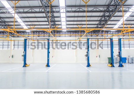 The electric lift for cars in the service put on the epoxy floor in new car factory service , Car repair service center blurred  background for industry  #1385680586