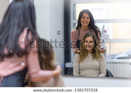Making hairstyle using hair dryer.  Portrait of a happy woman at the hair salon. Pretty brunette working as a hairdresser and cutting hair tips of a female customer in a beauty salon
