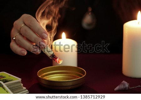 Witch is fortune teller in black mantle holding burning paper with spell over bowl. Tarot cards, amethyst stone, white candles on dark mystic background. Occult, esoteric, divination and wicca concept #1385712929
