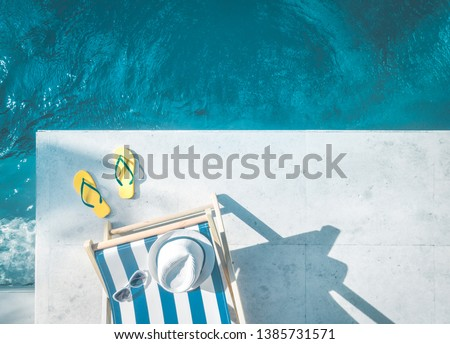 Aerial view of beach accessories next to the swimming pool #1385731571
