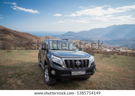 Alushta, Republic of Crimea - March 23, 2019: Black off-road car Toyota Land Cruiser Prado parked in nature #1385754149