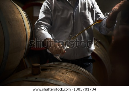 Man, pouring cognac from the barrel into glass in old rustic underground wine cellar with rows of big oak barrels. Famous wine and brandy industrial destination Royalty-Free Stock Photo #1385781704