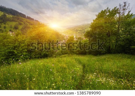 Panoramic view of beautiful landscape in the Alps with fresh green meadows and blooming flowers and snow-capped mountain tops in the background on a sunny day with blue sky and clouds in springtime. #1385789090