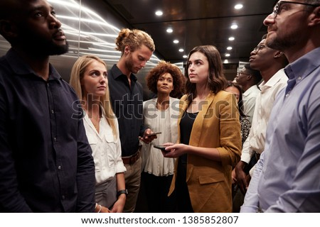 Work colleagues stand waiting together in an elevator at their office #1385852807
