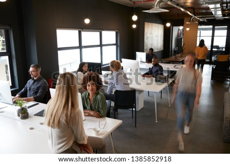 Elevated view of creative business colleagues working at desks and walking through a busy office
