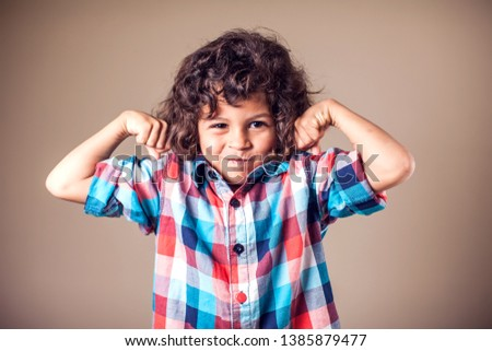 Portrait of a strong kid showing the muscles of his arms on grey background #1385879477