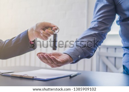 Soft Light,A young businessman has entered into a new car lease agreement in the office of the car dealer and accepts the car keys after completing the contract Concept of contract for car purchase