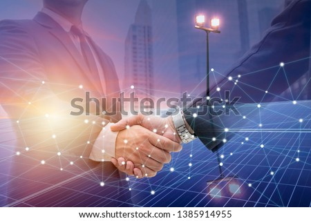 Businessmen are shaking hands for business venture and Marketing on energy.Solar is needed in the future.Solar panels require expertise in installation.photovoltaics to the business sector. #1385914955