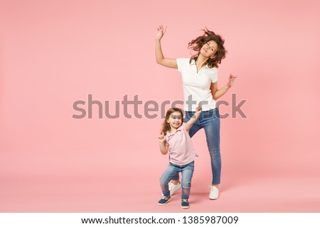 Woman in light clothes have fun with cute child baby girl. Mother, little kid daughter isolated on pastel pink wall background, studio portrait. Mother's Day love family, parenthood childhood concept #1385987009