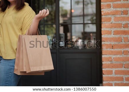 Young woman holding sale shopping bags. consumerism lifestyle concept in the shopping mall #1386007550
