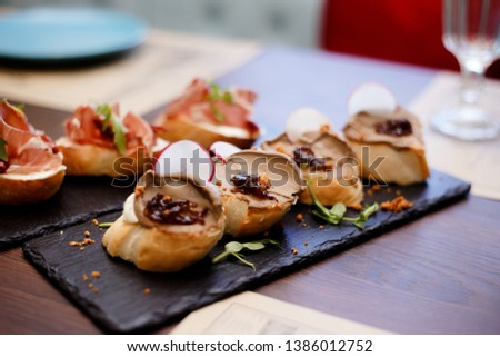 Toasted bread with liver pate. Gourmet appetizers, photo of sandwich on plate, crostini. Delicious. Front view. Assorted Italian appetizer bruschetta. Variety of mini sandwiches #1386012752
