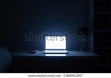 Room illuminated by a computer screen at night, no people. Empty workplace lit by a laptop display in the darkness, late work, overtime concept #1386061847