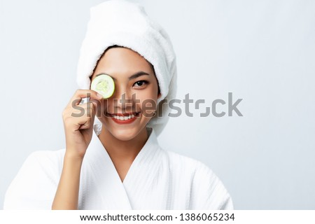 Natural homemade fresh cucumber facial eye pads facial masks. Asian woman holding cucumber pads and smile relax with natural homemade. #1386065234