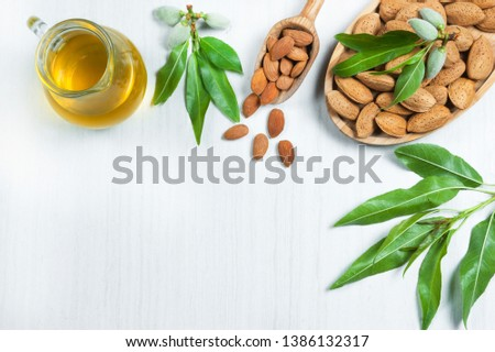 Top view Glass bottle of Almond oil and almond nuts in wooden shovel, almonds with shell in bamboo bowl on white table with green fresh raw almonds on almond tree branch #1386132317