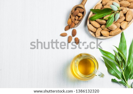 Top view Glass bottle of Almond oil and almond nuts in wooden shovel, almonds with shell in bamboo bowl on white table with green fresh raw almonds on almond tree branch #1386132320