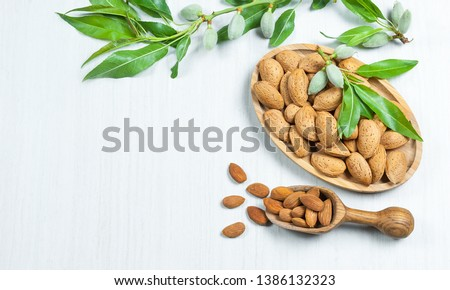 Top view Almond nuts in wooden shovel, almonds with shell in bamboo bowl on white table with green fresh raw almonds on almond tree branch. Almond background concept with copy space #1386132323