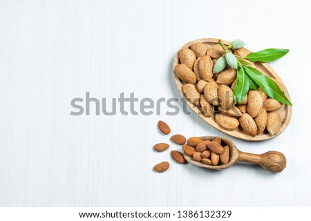 Top view Almond nuts in wooden shovel, almonds with shell in bamboo bowl on white table with green fresh raw almonds on almond tree branch. Almond background concept with copy space #1386132329