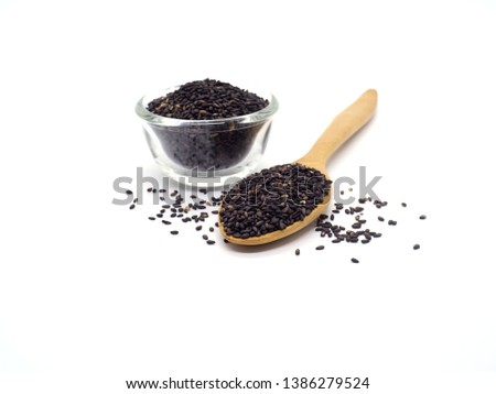 Black sesame in bowl and spoon isolated on white background.  #1386279524