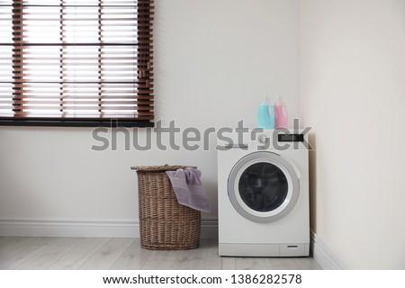 Modern washing machine and laundry basket indoors #1386282578