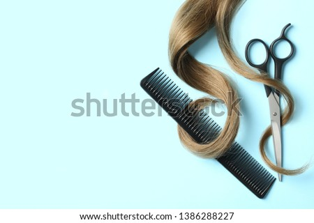 Flat lay composition with light brown hair, comb, scissors and space for text on color background. Hairdresser service Royalty-Free Stock Photo #1386288227